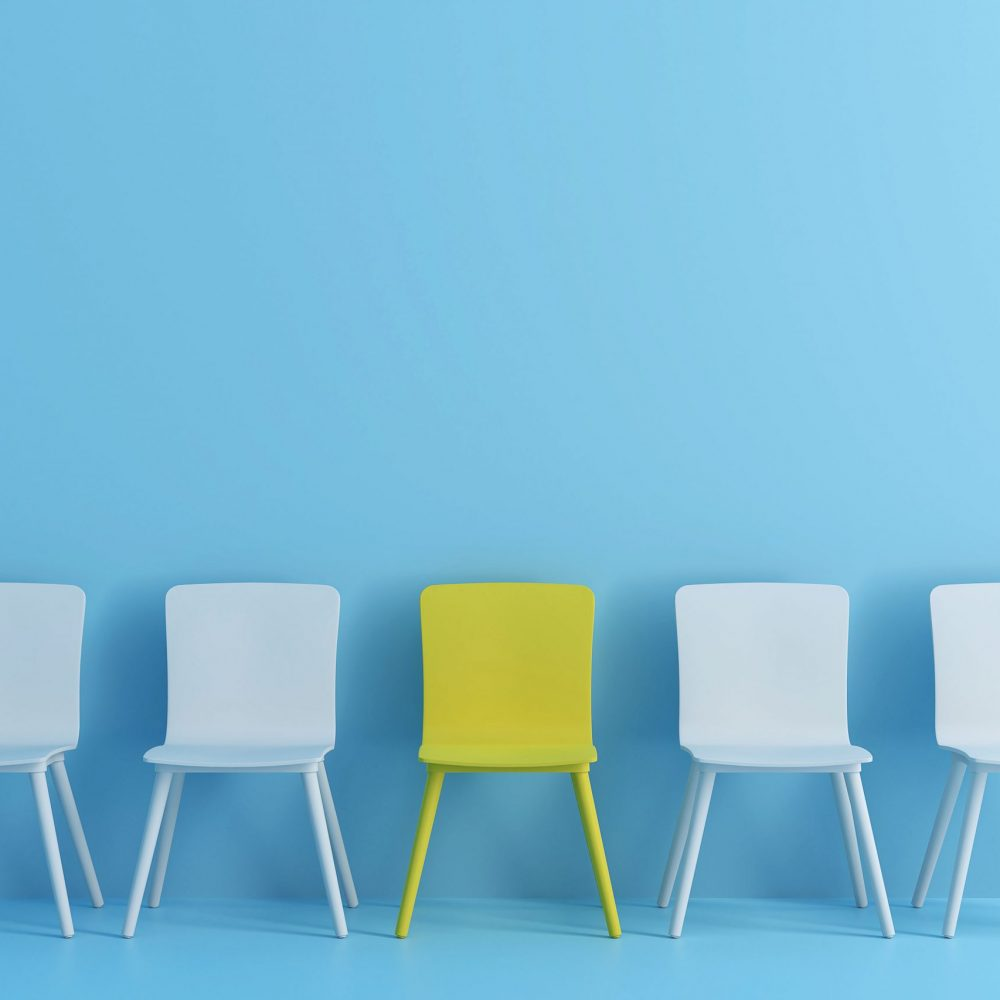 outstanding yellow chair among light blue chair. Chairs with one odd one out in light blue color room.